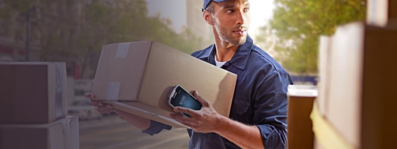 Delivery driver loading boxes into a truck while holding a handheld device that is managed and secured by SOTI MobiControl, which is Zebra Solution Validated